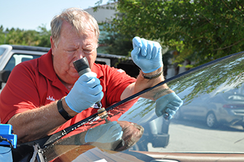 John McAuley, a SuperGlass Windshield Repair franchisee, repairs a windshield.