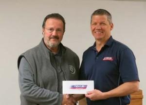 Steven Brashears, executive director of Feed Spokane accepts the $1,000 from Matt Anderson, owner of Novus Glass Spokane.