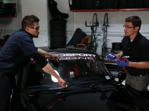 Kosilla (left) looks on while McCooey sets up his equipment for a windshield repair.
