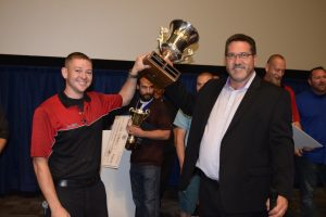 Mitch Trujillo (left) accepts the trophy from Troy Mason, owner of TechnaGlass.